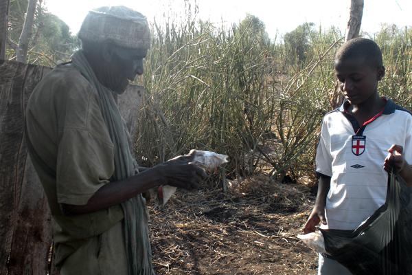 Mwambia Kiunga recieving a Ramadan food distribution from Salim Yassen.  (Photo by Salat James Sunday)