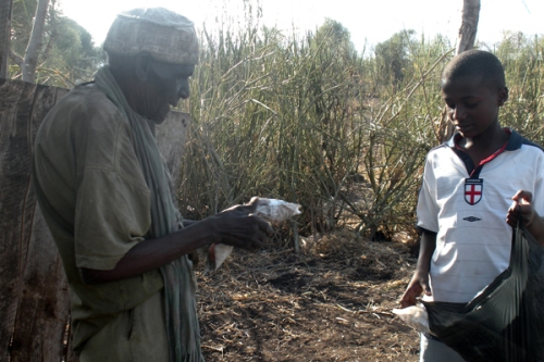 Mwambia Kiunga recieving a Ramadan food distribution from Salim Yassen.  (Photo by Salat James Sunday)